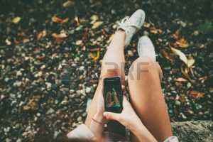 47120312-teenage-girl-taking-a-selfie-picture-of-her-feet-wearing-white-shoes-on-stony-lakeside