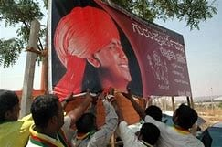 Protesters tearing down a hoarding of Nityananda Baba